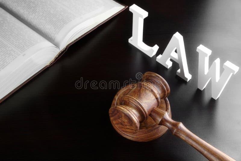 Martelo dos juizes, LEI vermelha do livro e do sinal na tabela preta fotografia de stock royalty free
