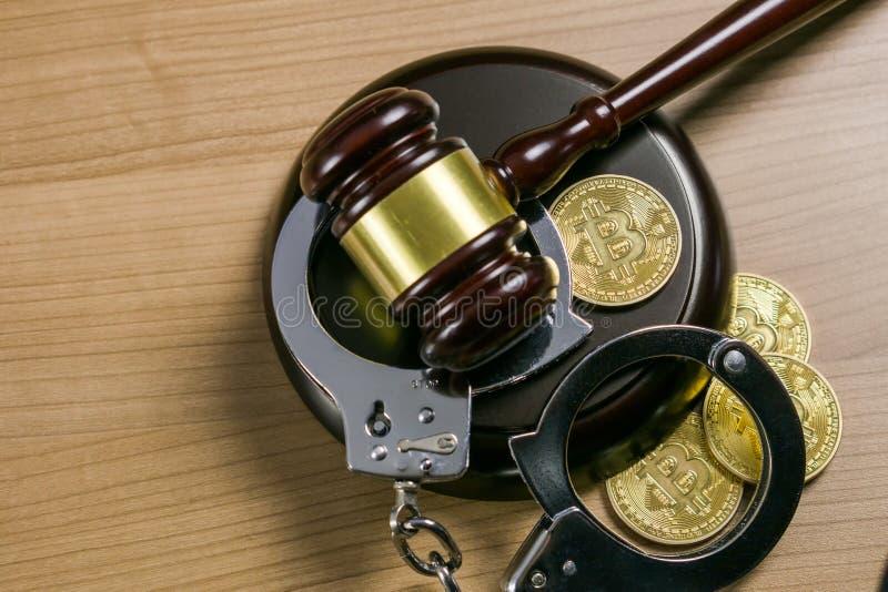 Martelo e algemas com bitcoins na mesa de madeira Conceito legal de Cryptocurrency foto de stock