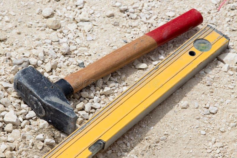 Martelo e ferramenta nivelada no terreno de construção imagens de stock royalty free