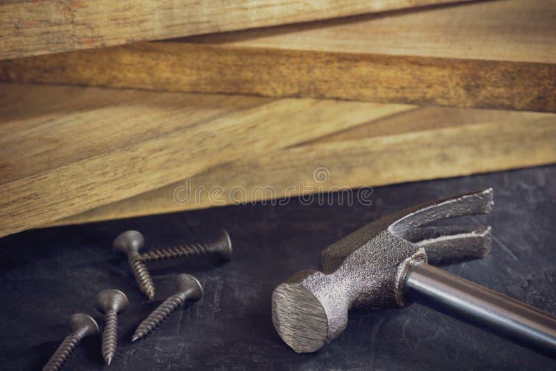 Martelo e parafuso na madeira serrada que empilha o fundo foto de stock