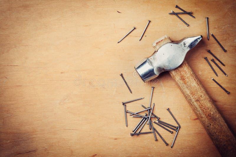 Martelo e pregos velhos no fundo rústico de madeira, ferramentas de funcionamento de cima de fotografia de stock