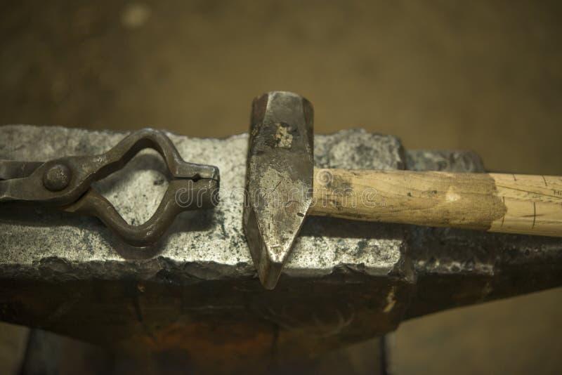 Martelo e tenazes de brasa no ferreiro Anvil fotos de stock