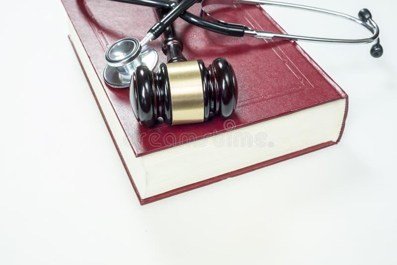 Martelo, estetoscópio e livro no fundo branco fotos de stock royalty free