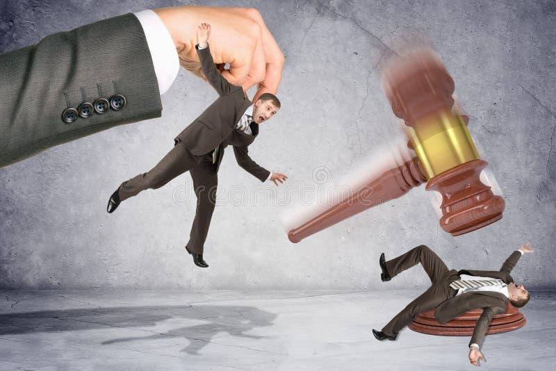 Martelo inscrito que bate o homem de negócios imagem de stock