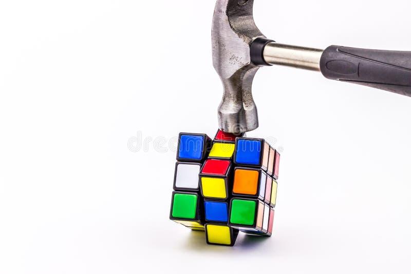 Martelo que despedaça o cubo de Rubik foto de stock royalty free
