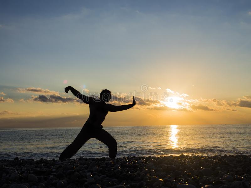 Martial Artist with orange sunset. Silhouette of a man practice whushu. Healthy lifestyle stock image