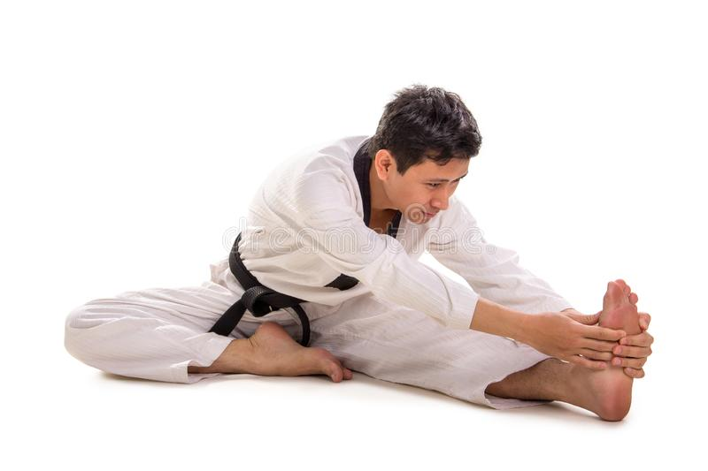 Full body legs and torso stretch on the floor, full length shot. Martial artist stretches his body on the floor, bends his torso toward his leg, wraps a royalty free stock photography