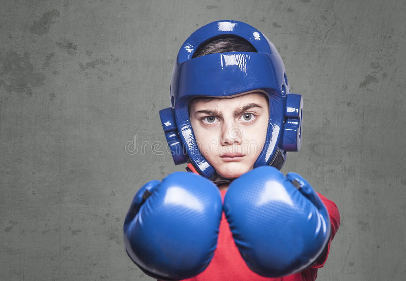Martial arts kids concept. Determined little fighter wearing gloves and helmet royalty free stock photography