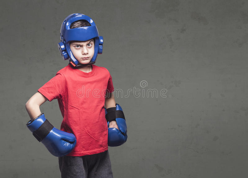 Martial arts kids concept. Determined little fighter wearing gloves and helmet stock photo