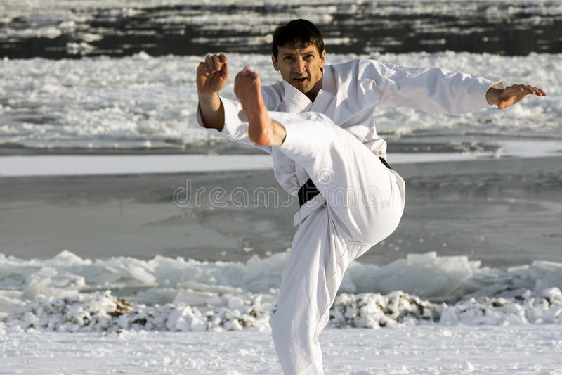 Martial arts in snow. Man in white kimono is practicing karate shot barefoot in the snow outdoors at winter stock images