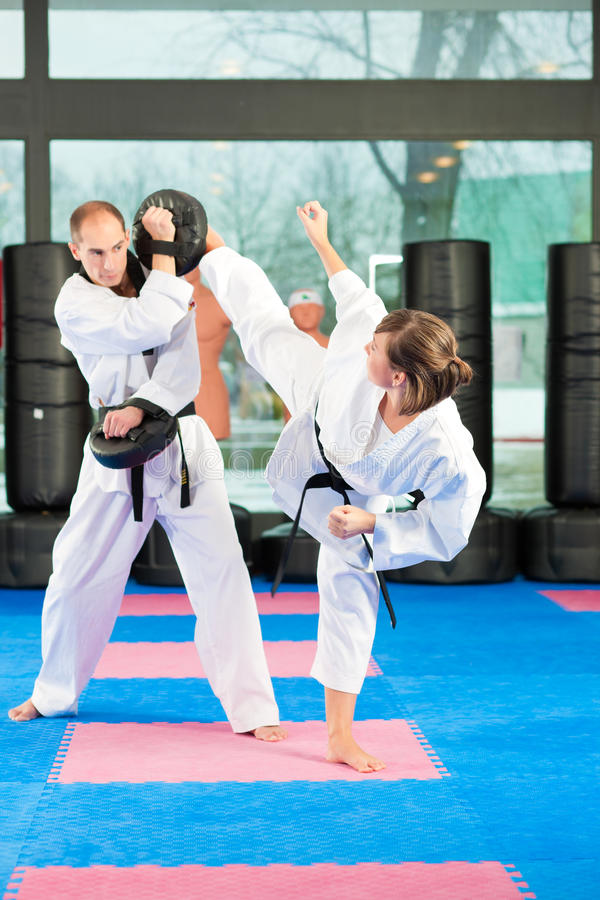 Martial Arts sport training in gym. People in a gym in martial arts training exercising Taekwondo, both have a black belt royalty free stock image