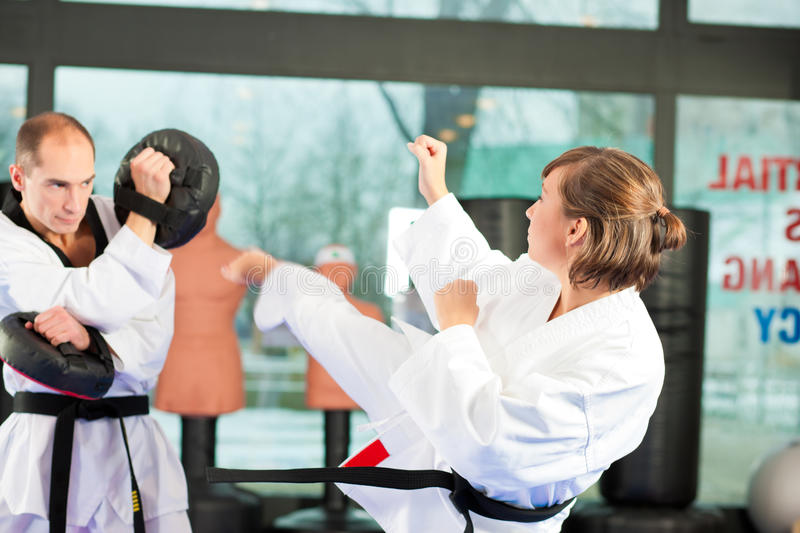 Martial Arts sport training in gym. People in a gym in martial arts training exercising Taekwondo, both have a black belt royalty free stock photography