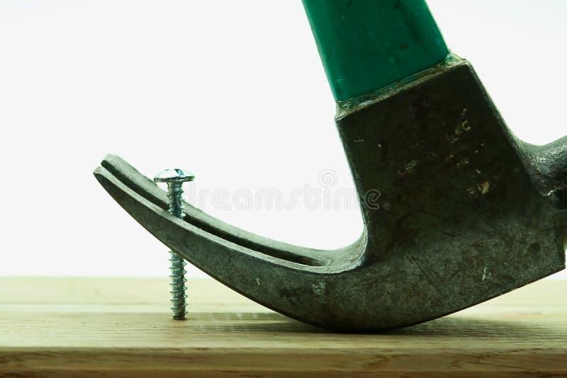 Martillo de garra que intenta quitar el tornillo de la madera fotos de archivo