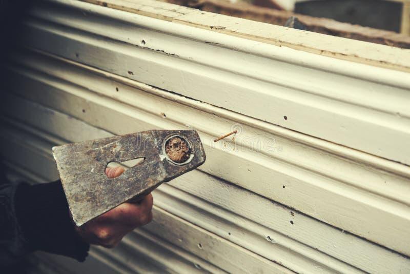 Martillo de la mano del hombre con el clavo imagen de archivo libre de regalías