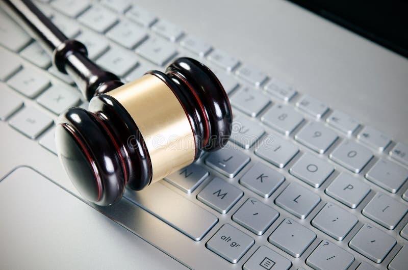 Martillo de madera del juez en el ordenador portátil fotografía de archivo