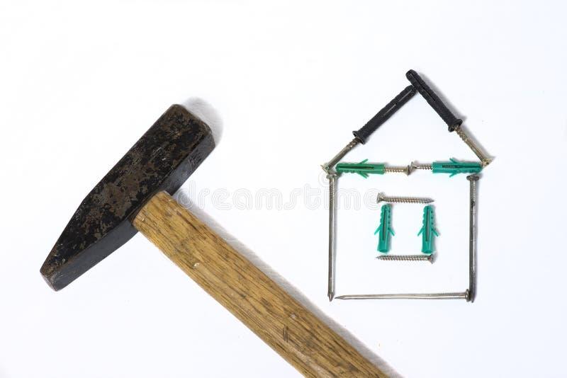 Martillo del hierro con la casa de clavo de madera de la manija en el fondo blanco foto de archivo