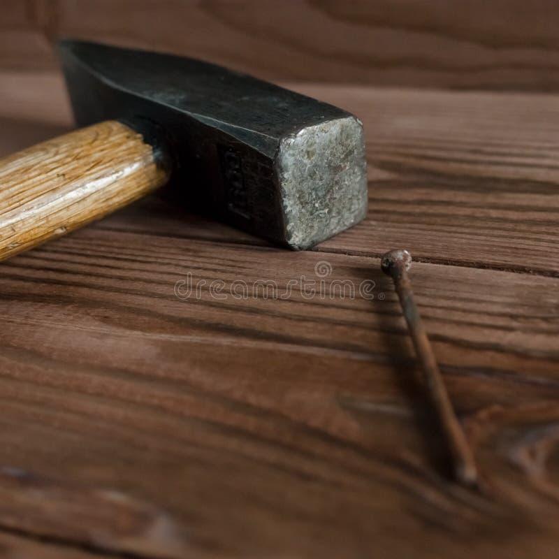 Martillo usado viejo, manija de madera, cabeza del metal y clavo oxidado en el contexto de madera imagen de archivo libre de regalías