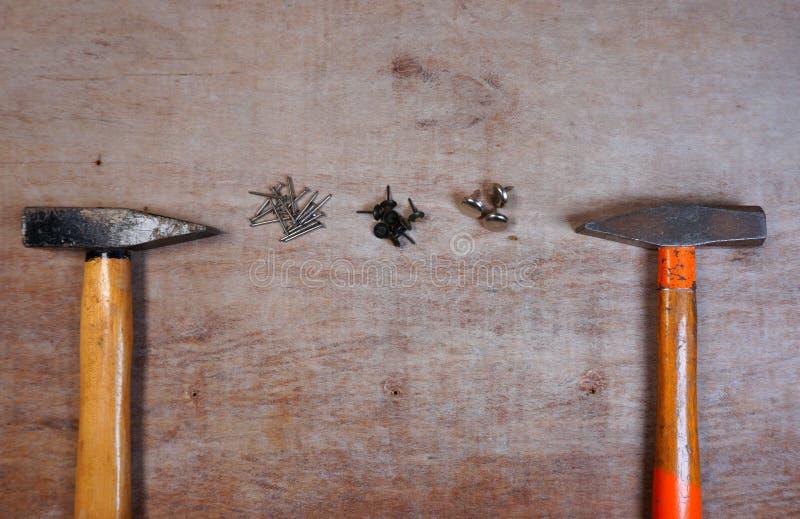 Martillo y clavos en un fondo de madera del tablero imagen de archivo libre de regalías