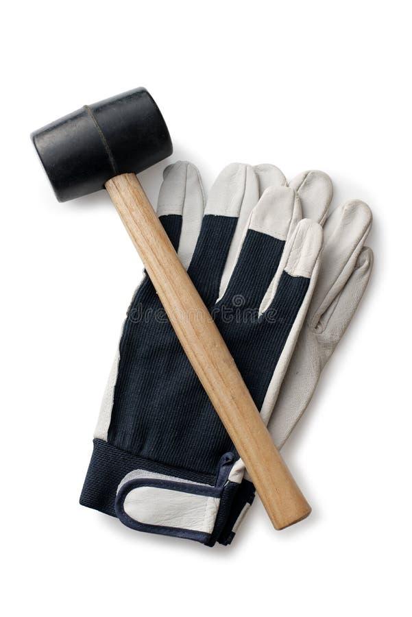 Martillo y guantes de goma en un fondo blanco fotografía de archivo libre de regalías