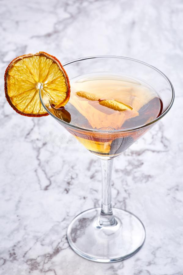Martinez cocktail with dried orange slice and cedar. Yellow drink in martini glass at white marble backdrop. Classic alcohol cocktail stock photos
