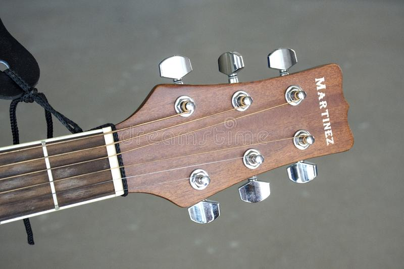 Martinez`s brown guitar neck with tuning pegs on a gray background. St. Petersburg, Russia - May 24, 2019: Martinez`s brown guitar neck with tuning pegs on a stock images