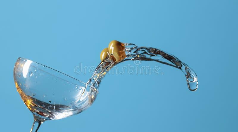 Martini με τα πράσινα χυσίματα ελιών από το γυαλί στοκ εικόνα