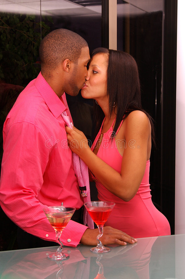 Martini Bar Kiss. African American couple share a kiss in a martini bar stock images
