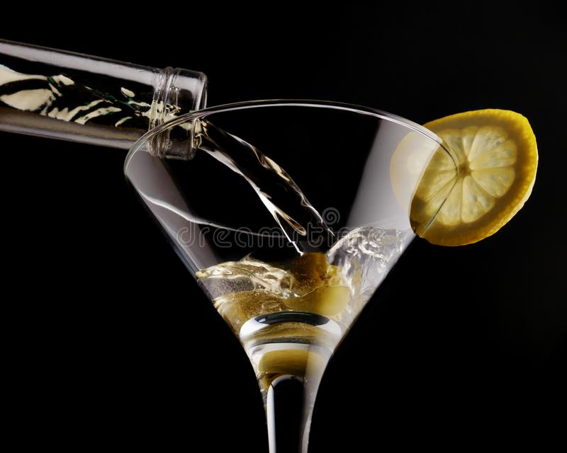 Martini classique en verre effrayant au-dessus du fond noir, garni avec l'olive et le citron photographie stock libre de droits