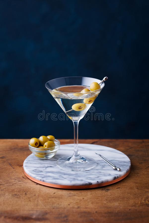 Martini coctail med gröna oliv på marmorbräde table trä background card congratulation invitation fotografering för bildbyråer