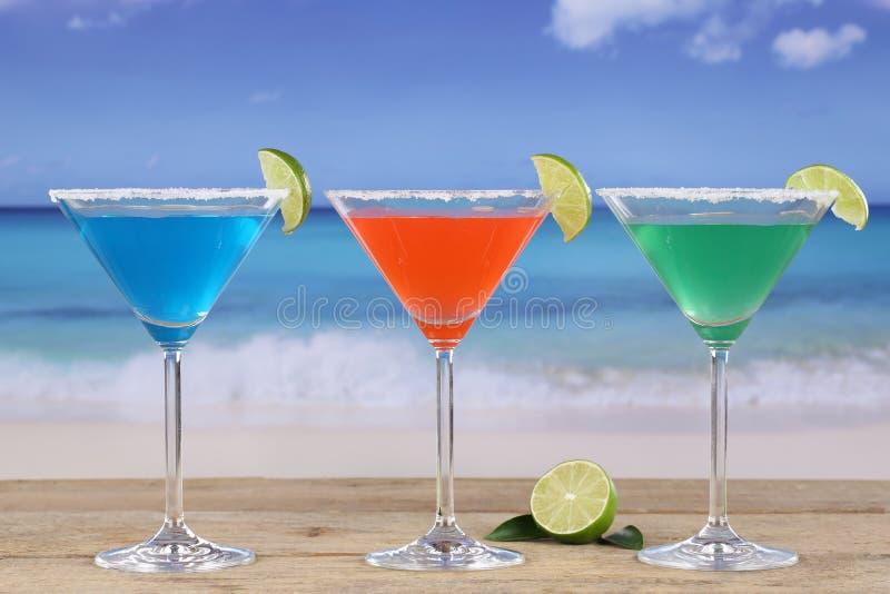 Martini coctailar i exponeringsglas på stranden med citroner arkivfoto