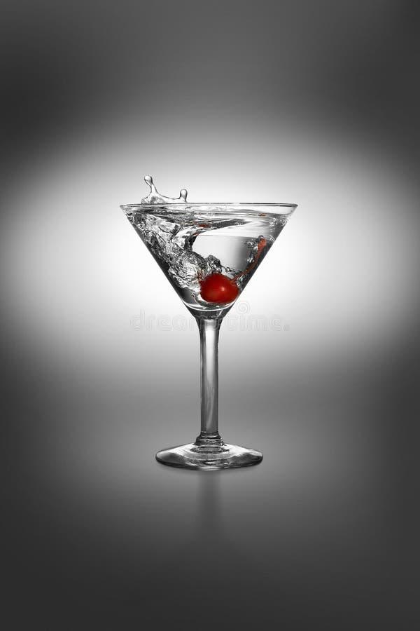 Martini con el chapoteo de la cereza foto de archivo