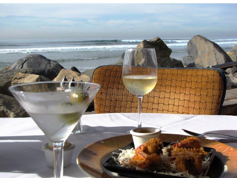 Martini con las aceitunas y el vino blanco más los aperitivos en la playa imagen de archivo