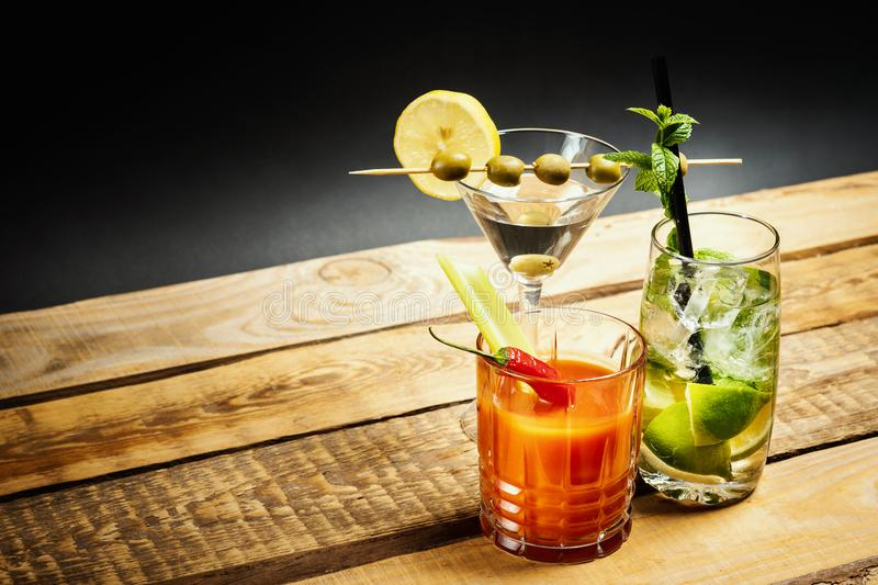 Martini drink with olive and mojito with mint and bloody mary with celery royalty free stock photos