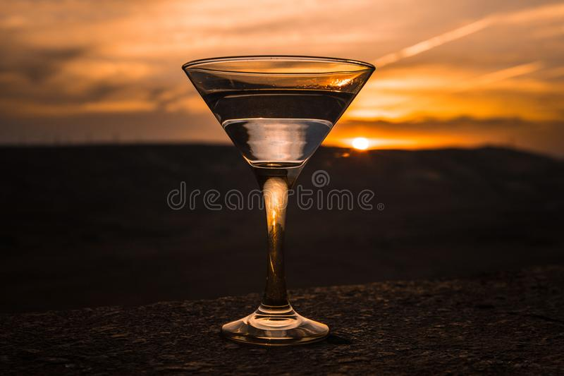 Martini in a glass against sunset background with mountains. Club drink at sunset time royalty free stock photo