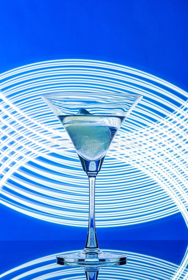 Martini glass on a blue background cocktail ice light. Martini glass on a blue background cocktail bar evening light advertising ice royalty free stock photography