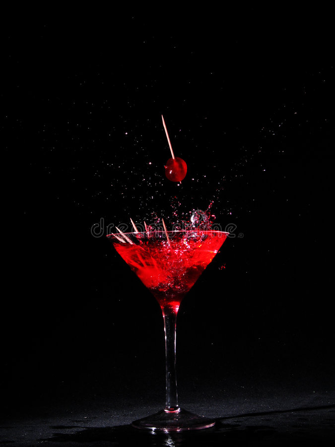 Martini glass with cherries. Martini glass with red cherries on toothpicks royalty free stock images