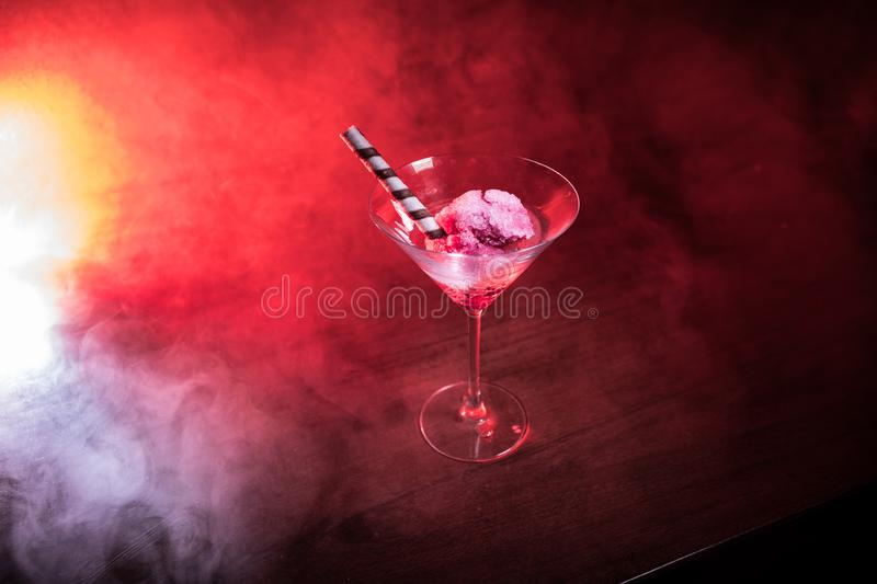 Martini glass filled with colorful fruit ice cream on dark background with toned light and fog. Selective focus royalty free stock photo