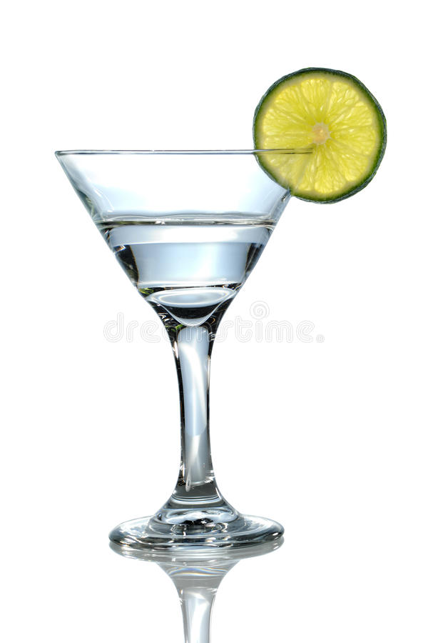 Martini Glass With Lime. Martini glass with clear liquid and lime over white background - With Clipping Path stock photography