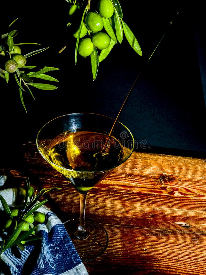 Martini glass with olive oil and olives stock photography