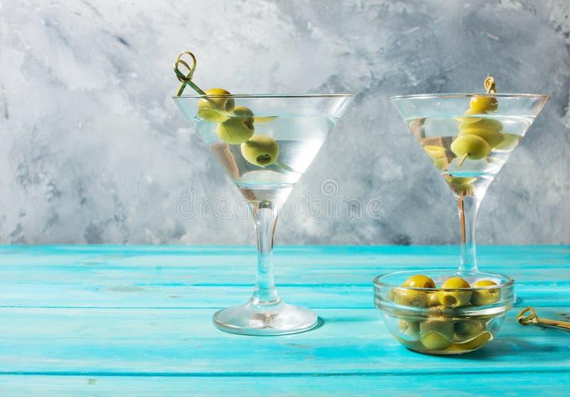 Martini koktajl z zielonymi oliwkami na błękitnym drewnianym tle obrazy stock