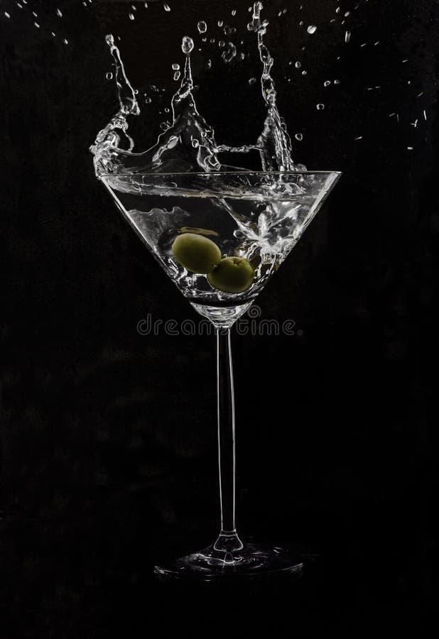 Martini met en olijven die vallen bespatten royalty-vrije stock foto's