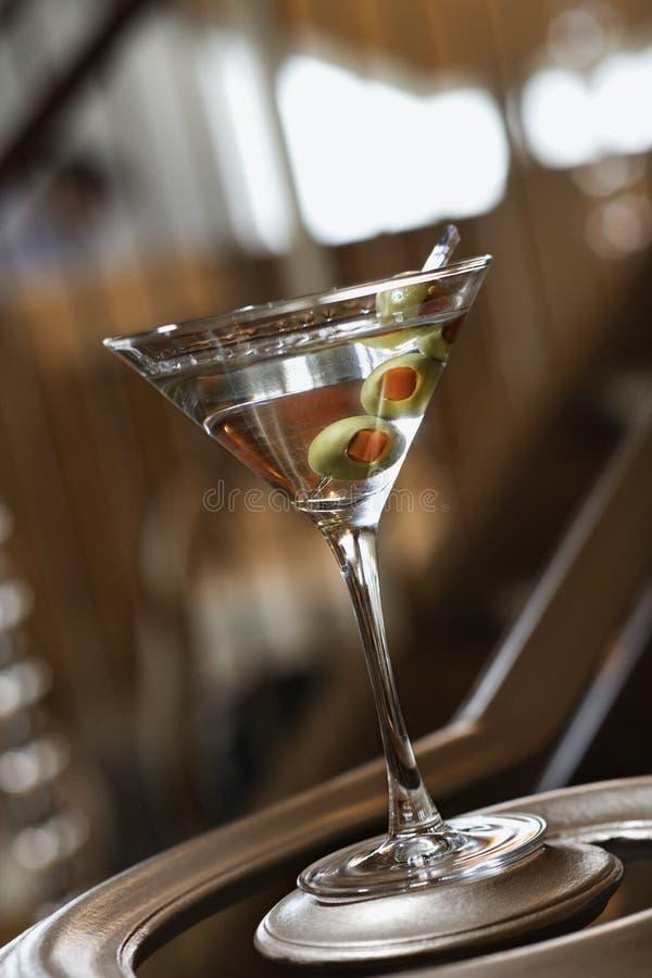 Martini mit Oliven auf Geländerdocke stockbild