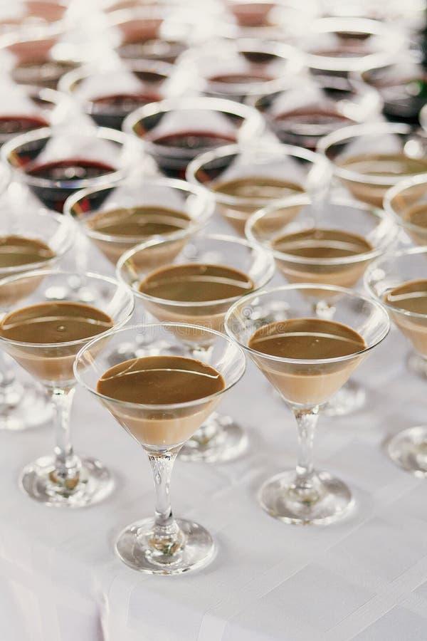 Martini rader på tabellen på bröllopmottagandet Coctailar och röda och vita martini i exponeringsglas på alkoholstången på bröllo royaltyfria bilder