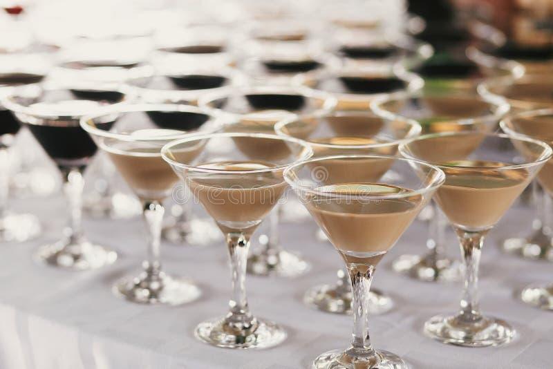 Martini-rijen op lijst bij huwelijksontvangst Cocktails en rode en witte martini in glazen bij alcoholbar bij huwelijk of Kerstmi royalty-vrije stock afbeeldingen