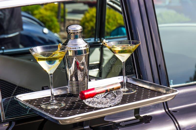 Martini shaker, exponeringsglas, magasin för Ash Tray And Cigar On Car flygturportion fotografering för bildbyråer