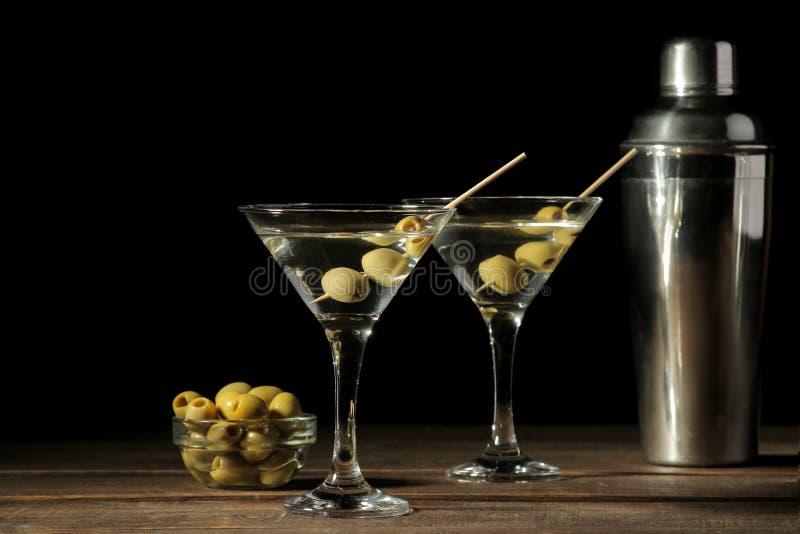 Martini wineglass γυαλιού με τις πράσινες ελιές σε ένα οβελίδιο σε έναν καφετή ξύλινο πίνακα κοκτέιλ ράβδος στοκ φωτογραφία