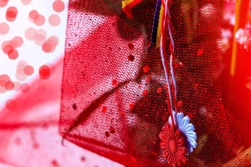 Martisor met Roemeense tricolorelementen op rode vakantieachtergrond Moldavisch en Roemeens de lente en liefdesymbool Martisor is stock foto
