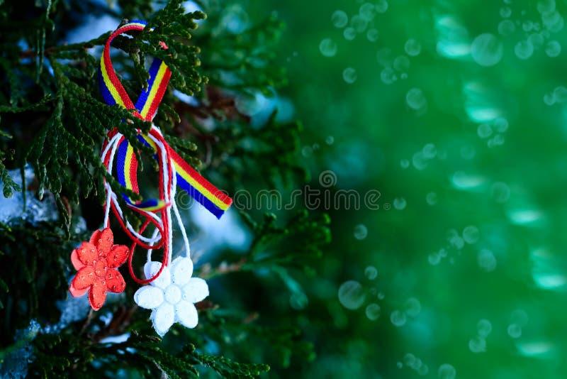 Martisor su sfondo naturale verde - moldavo e simbolo rumeno della molla Martisor è una corda rossa e bianca che è offerta immagine stock libera da diritti
