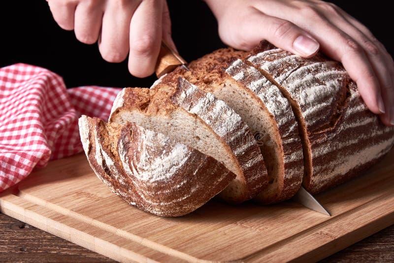 Martwa natura z chlebem w plasterkach Kobieta trzymająca nóż kuchenny Stary drewniany stół biurkowy obraz royalty free