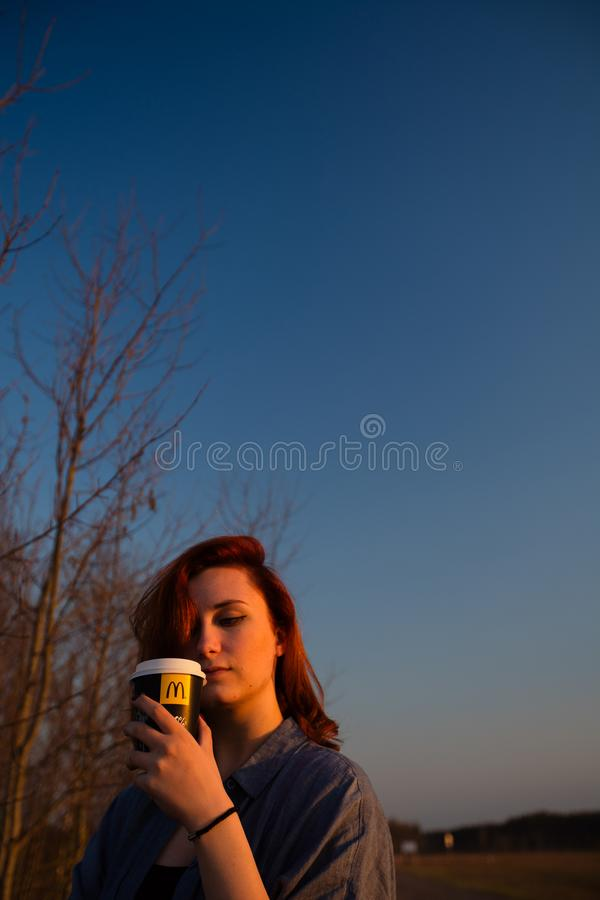 MARUPE, LATVIA - APRIL 22, 2019: Young woman drinking McDonalds coffee outdoors in a field during sunset royalty free stock photos